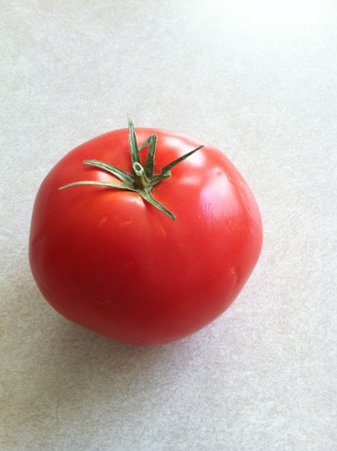 A red, ripe tomato sitting on a kitchen counter
